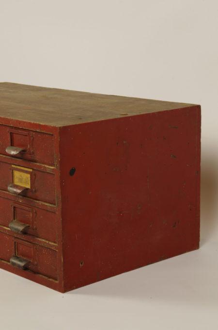Oude houten ladekastje in warm rood